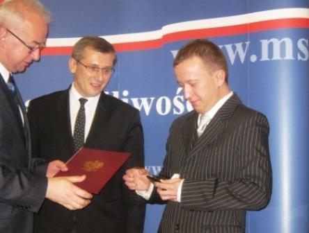 2010.11.04 Pan Tomasz Łotoczko przyjmuje odznaczenie resortowe zrąk  Pana Ministra Sprawiedliwości iPana Wiceministra Sprawiedliwości